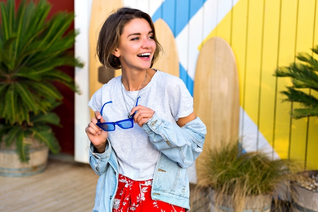 Summer spring bright positive portrait of happy smiling brunette woman wearing trendy feminine hipster outfit smiling and having fun, posing in front of surf boards and palms.