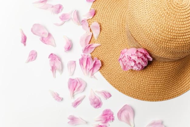 夏、春のコンセプト、わらの編みこみの帽子、白い表面にピンクの牡丹の花と花びら、上面図