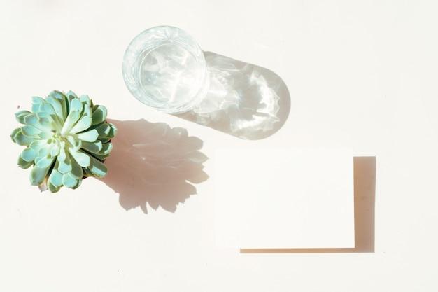 여름 문구 목업 장면입니다. 중성 베이지색 바탕에 빈 명함과 맑은 물 한 잔.