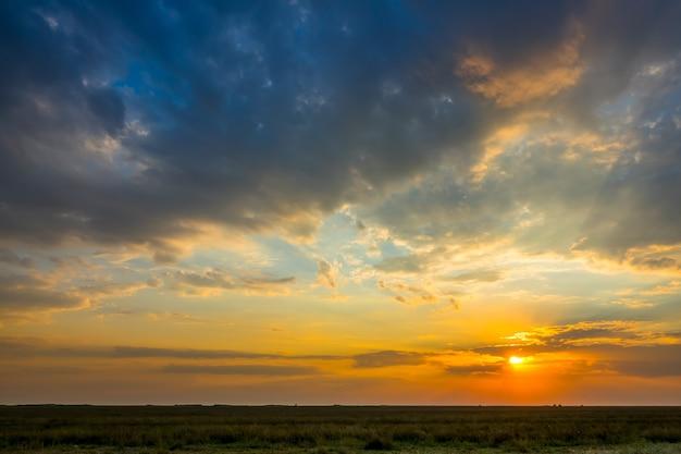 夏の草原。照らされた雲とカラフルな夕日