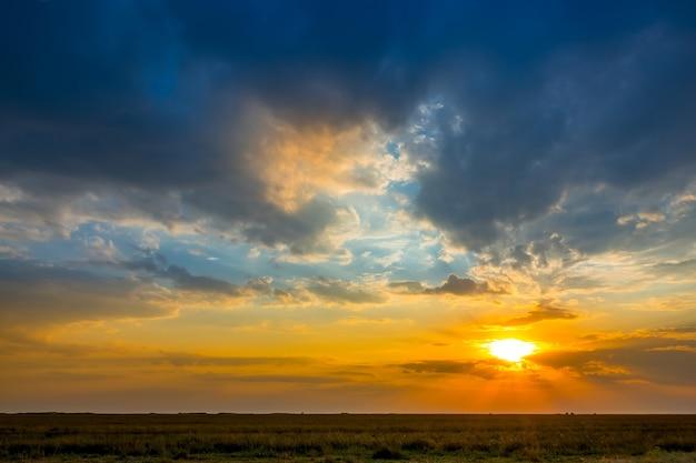 夏の草原平野。照らされた雲とカラフルな夕日