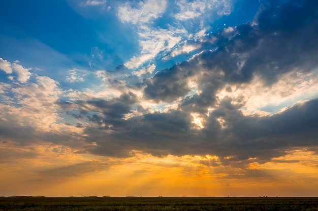 夏の草原平野。多くの照らされた雲とカラフルな夕日