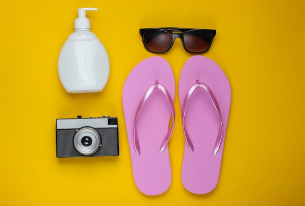 Summer still life. beach accessories. fashionable beach pink flip flops, retro camera, sunblock bottle, sunglasses, seashell on yellow paper background.