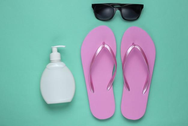 夏の静物。ビーチアクセサリー。ファッショナブルなビーチピンクのビーチサンダル、日焼け止めボトル、サングラス、青い紙の背景に貝殻。