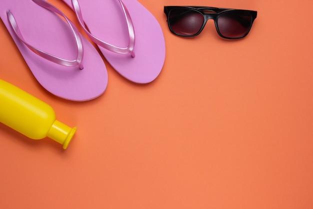 夏の静物。ビーチアクセサリー。ファッショナブルなビーチピンクのビーチサンダル、日焼け止めボトル、サングラス、珊瑚紙の背景に貝殻。