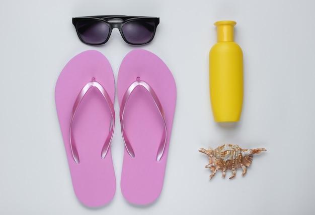 夏の静物。ビーチアクセサリー。ファッショナブルなビーチピンクのフリップフロップ、日焼け止めボトル、サングラス、白い紙の背景に貝殻。