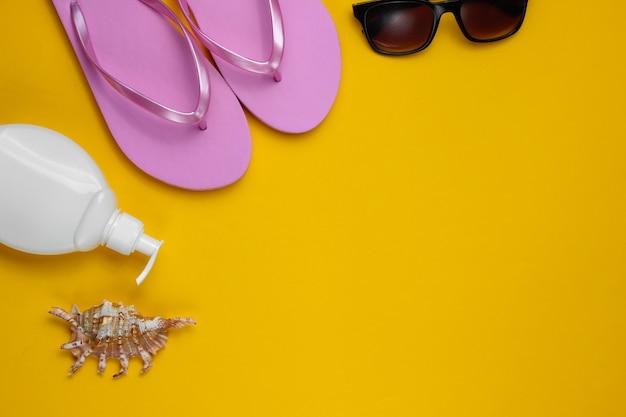 夏の静物。ビーチアクセサリー。ファッショナブルなビーチピンクのビーチサンダル、日焼け止めボトル、サングラス、黄色い紙の背景に貝殻。フラットレイ。コピースペース。上面図