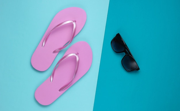 Summer still life. beach accessories. fashionable beach pink flip flops, sunglasses on blue  paper background. flat lay. top view