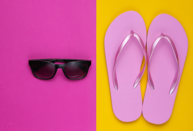 Summer still life. beach accessories. fashionable beach pink flip flops, sunglasses on colored paper background. flat lay. top view