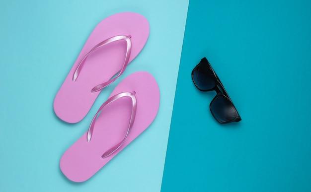 Летний натюрморт. пляжные аксессуары. модные пляжные розовые шлепки, солнцезащитные очки на синем бумажном фоне. плоская планировка. вид сверху