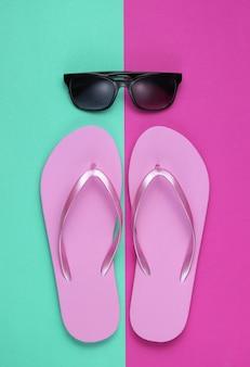Летний натюрморт. пляжные аксессуары. модные пляжные розовые шлепки, солнцезащитные очки на розовом синем бумажном фоне.