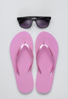Летний натюрморт. пляжные аксессуары. модные пляжные розовые шлепки, солнцезащитные очки на фоне белой бумаги.