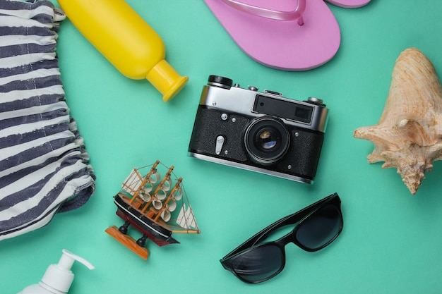 Summer still life. beach accessories. fashionable pink flip flops, bag, retro camera, sunblock bottle, sunglasses, seashell on blue paper background.