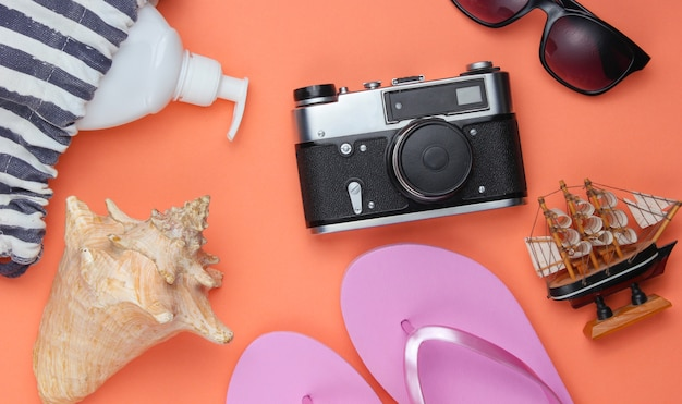 Summer still life. beach accessories. fashionable pink flip flops, bag, retro camera, sunblock bottle, sunglasses, seashell on coral paper background.