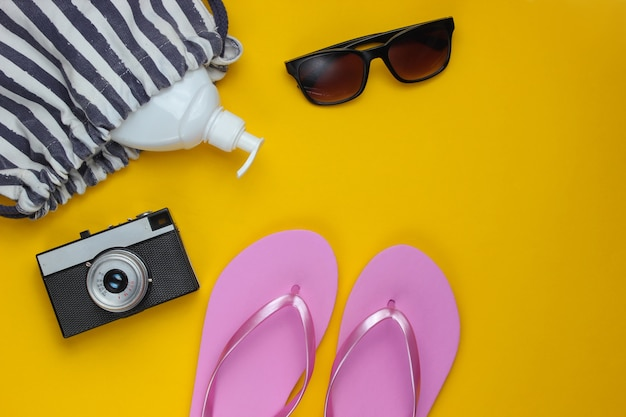 Summer still life. beach accessories. fashionable pink flip flops, bag, retro camera, sunblock bottle, sunglasses, seashell on yellow paper background.