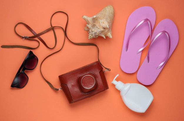 Summer still life. beach accessories. fashionable pink flip flops, retro camera, sunblock bottle, sunglasses, seashell on coral paper background.