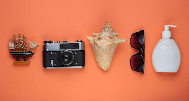 Summer still life. beach accessories. retro camera, sunblock bottle, sunglasses, seashell on coral paper background.