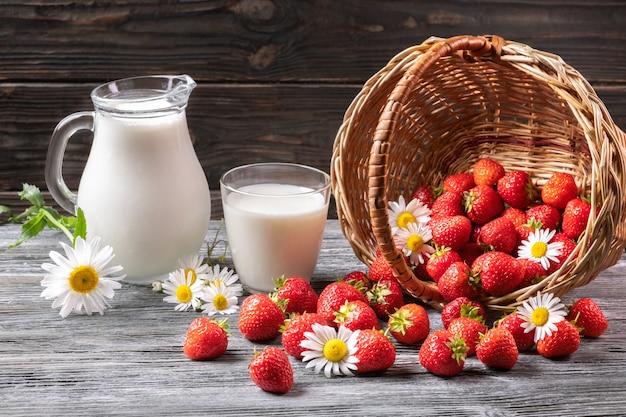 Летний натюрморт, ягоды, молоко и ромашка на старой доске. Premium Фотографии