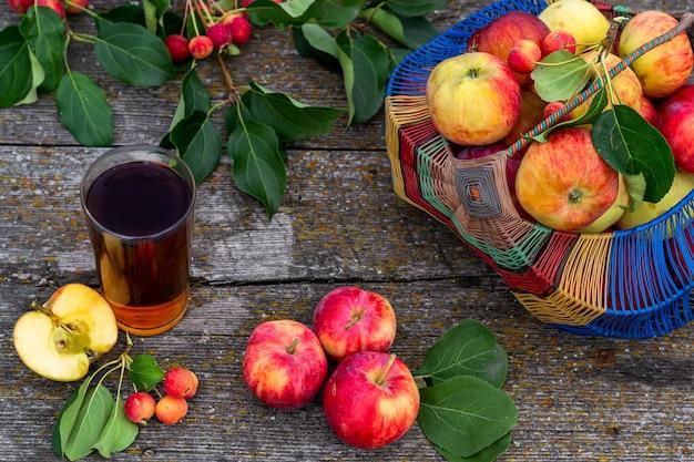 素朴なスタイルの夏の静物、バスケットに熟した庭のリンゴ、テーブルの上に横たわる、リンゴジュースのグラス。水平方向の写真のクローズアップ。