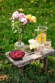 Summer still life: juice, apple, flowers, raspberries. rustic berries, fruits and flowers.