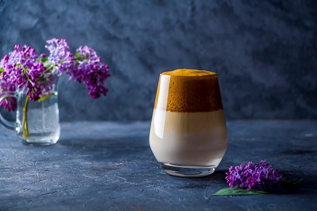 키가 큰 유리에 달고나 커피와 어두운 배경에 라일락 꽃 여름 아직도 인생. 설탕과 물로 채운 인스턴트 커피는 차가운 우유에 첨가됩니다.
