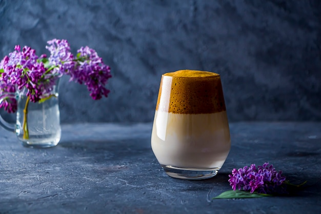 Summer still life with dalgona coffee in tall glass and lilac flowers on dark background. instant coffee whipped with sugar and water and added to cold milk.