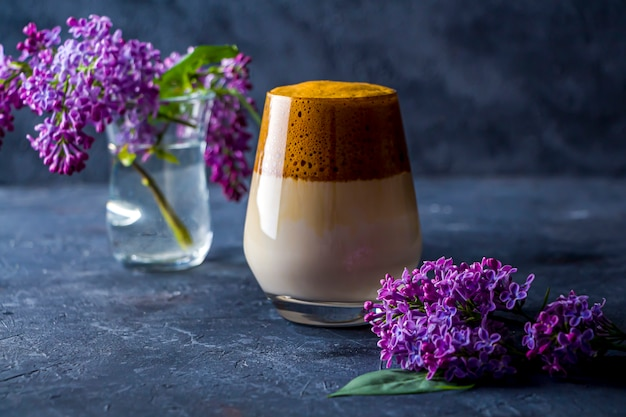 Summer still life with dalgona coffee in tall glass and lilac flowers on dark. instant coffee whipped with sugar and water and added to cold milk.