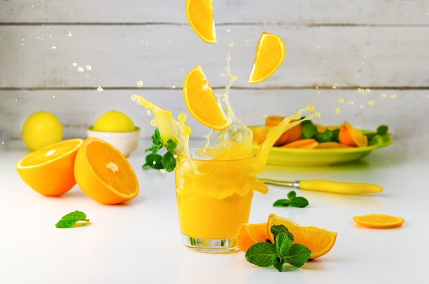 Summer still life with orange juice splash and mint on white . healthy lifestyle .