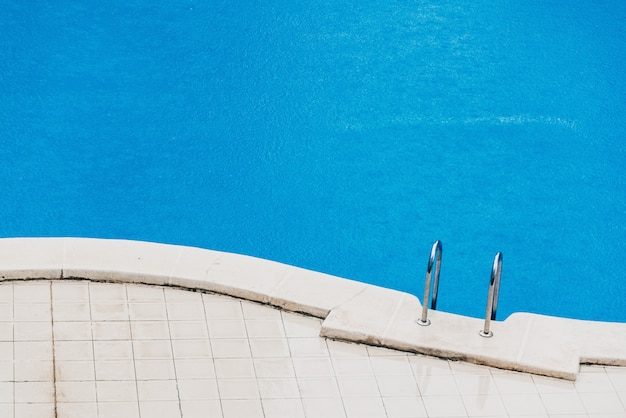 Summer storm, a fine rain falls on the blue water of a swimming pool in a hotel.