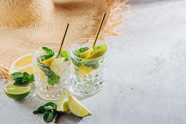 Летняя соломенная шляпа и свежий цитрусовый лимонад. концепция летних каникул