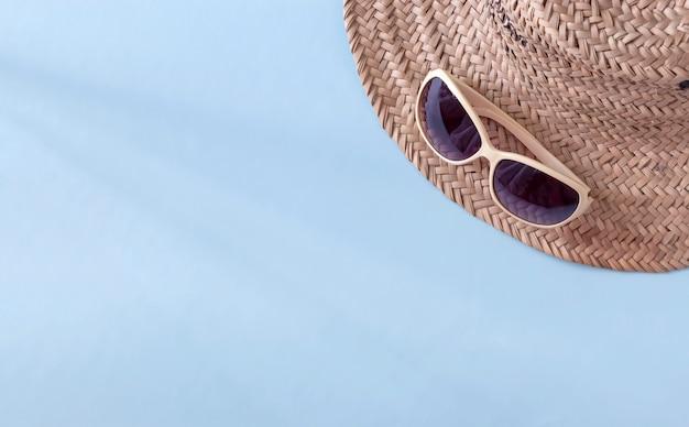Летняя соломенная шляпа и солнцезащитные очки на голубой поверхности