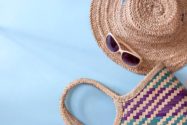 Летняя соломенная шляпа, соломенная сумка и солнцезащитные очки на голубой поверхности