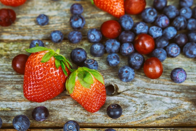 Summer strawberry, blueberries on wooden table background.