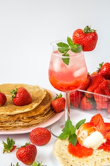 Summer strawberry season. strawberries with pancakes and ice cream and water with ice and strawberry syrup.