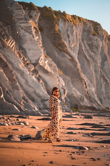 Summer street style on a beach next to rocks of a young brunette caucasian woman in a leopard dress. sakoneta beach in the town of deba, basque country.