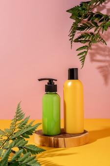 Летний стиль витрины для отображения косметической продукции на желтом фоне. зеленые и желтые бутылки косметических продуктов на деревянном подиуме.
