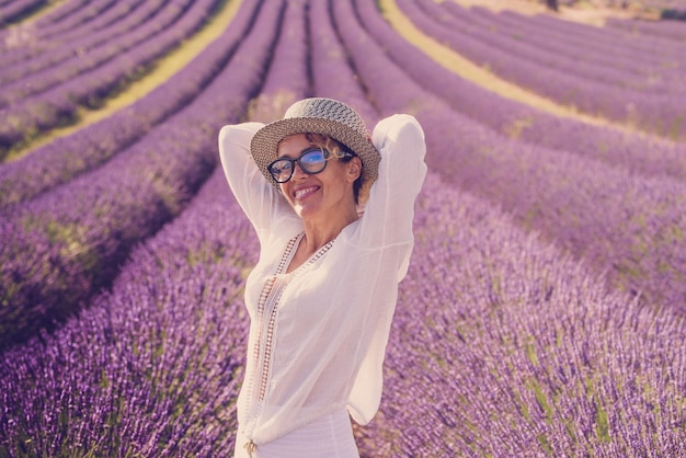 Summer style portrait of cute middle age woman smiling and having fun with violet flowers of lavender fields in background - travel people and outdoor scenic europe places concept lifestyle