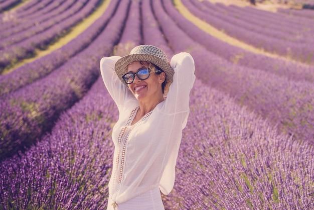 背景のラベンダー畑の紫色の花を笑顔で楽しんでいるかわいい中年女性の夏のスタイルの肖像画-旅行者と屋外の風光明媚なヨーロッパの場所のコンセプトライフスタイル