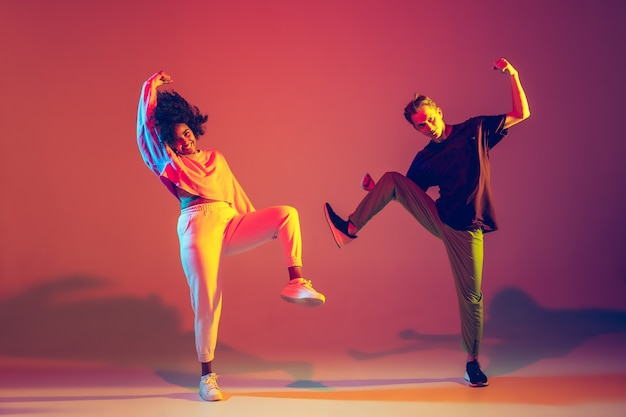 Лето. стильный мужчина и женщина танцуют хип-хоп в яркой одежде на зеленом фоне в танцевальном зале в неоновом свете. молодежная культура, движение, стиль и мода, действие. модный портрет.