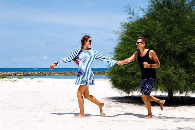 Summer sun portrait of cute couple having romantic vacation in tropical island .running and going crazy together.