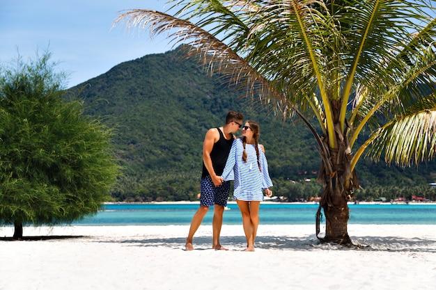 熱帯の島でロマンチックな休暇を持っているかわいいカップルの夏の太陽の肖像