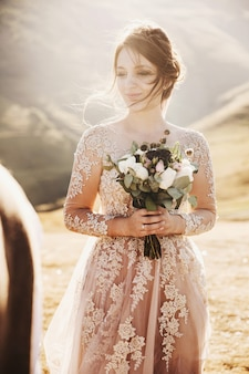 Summer sun shines over stunning bride standing on the top of georgian mountains