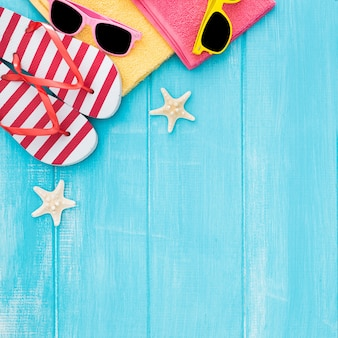 Summer sunbathing beach wooden background, sunglasses, flip flops, copy space
