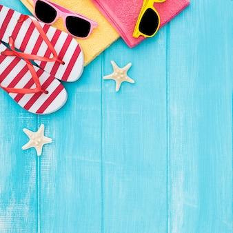 夏の日光浴、ビーチの木製の背景、サングラス、フリップフロップ、コピースペース