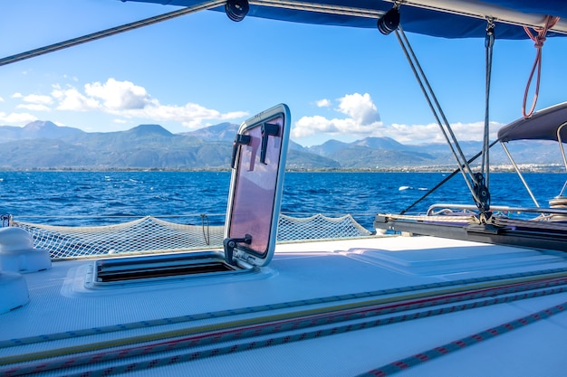 Summer sunny day aboard a sailing yacht. rigging and mast. view of the hilly coast