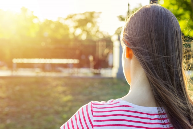 Summer sunny day. back view. young girl sits in a park on a bench and reads a book.