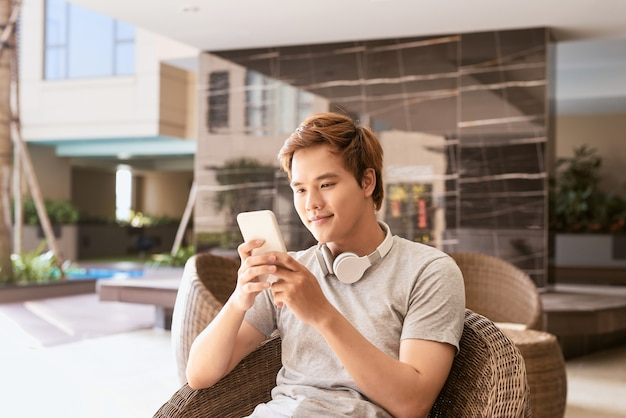 Summer sunny day, cheerful attractive smile asian man uses the smartphone
