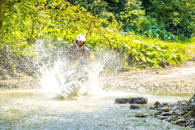 Summer sunny day in the forest. enduro athlete overcomes a shallow stream with lots of water splashes