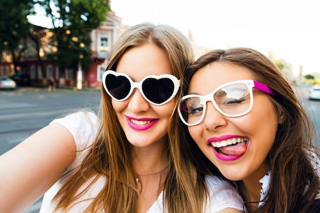Immagine soleggiata di estate di due sorelle migliori amiche bruna e ragazze bionde che si divertono per strada, facendo selfie, indossando occhiali da sole vintage divertenti, trucco elegante luminoso i capelli lunghi