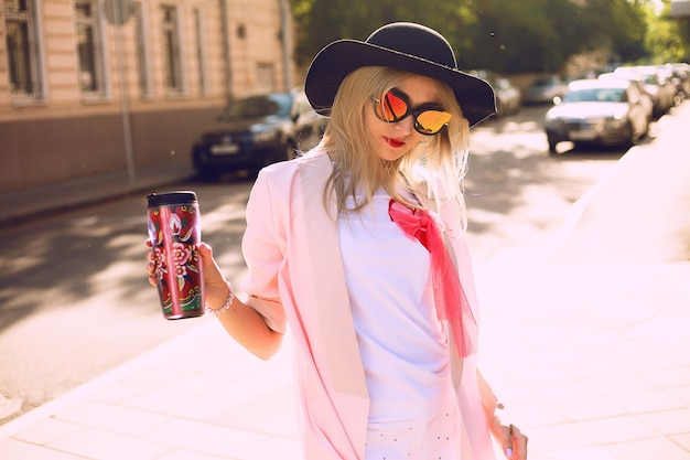 通りを歩いて、かわいい流行の服を着て、熱いラテを飲む若いスタイリッシュな流行に敏感な女性の夏の日当たりの良いライフスタイルファッションの肖像画